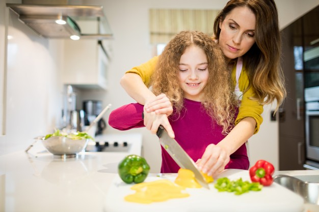 mother-assisting-daughter-in-cutting-vegetables-in-kitchen_1170-2823.jpg